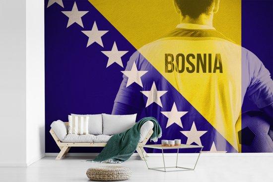 Fotobehang vinyl - Voetballer achter de vlag van Bosnië en Herzegovina breedte 360 cm x hoogte 240 cm - Foto print op behang (in 7 formaten beschikbaar)