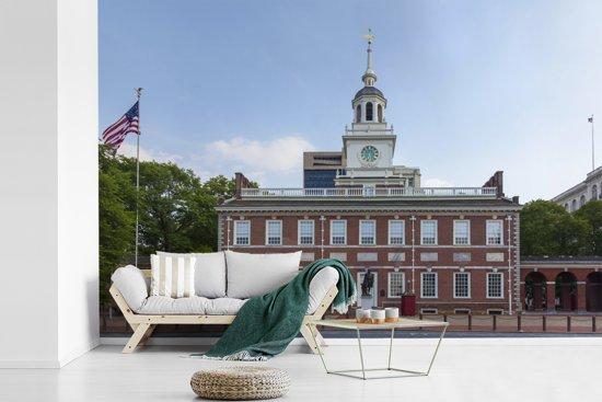 Fotobehang vinyl - Independence Hall met een wapperende Amerikaanse vlag breedte 360 cm x hoogte 240 cm - Foto print op behang (in 7 formaten beschikbaar)