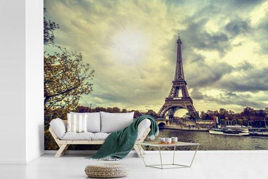 Fotobehang vinyl - Uitzicht over het water op de Eiffeltoren en Parijs breedte 600 cm x hoogte 400 cm - Foto print op behang (in 7 formaten beschikbaar)