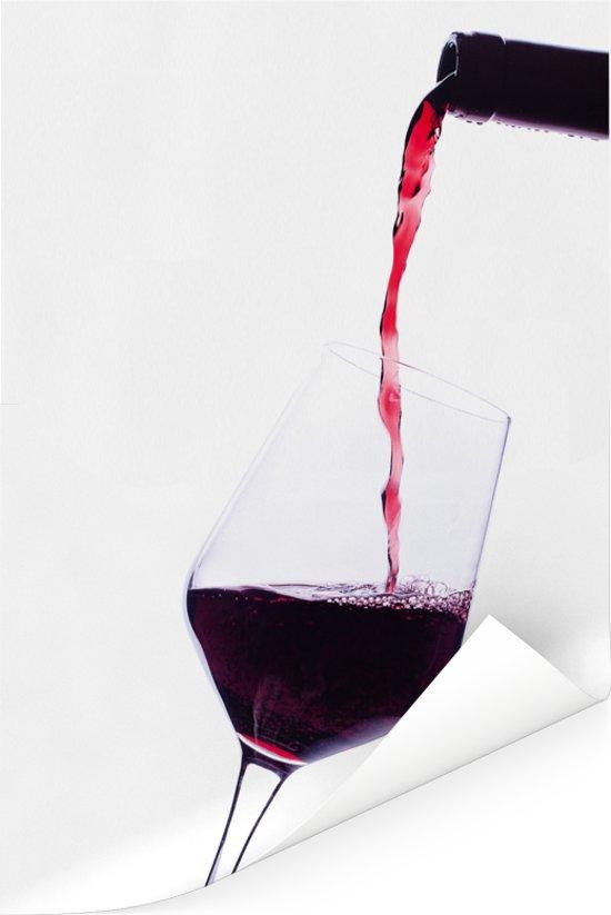Fles wijn wat rode wijn in het glas schenkt Poster 60x90 cm - Foto print op Poster (wanddecoratie woonkamer / slaapkamer)