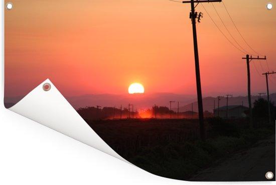 Een afbeelding van de zonsondergang bij een weg met elektrische polen in het prachtige Santa Marta Tuinposter 90x60 cm - Tuindoek / Buitencanvas / Schilderijen voor buiten (tuin decoratie)