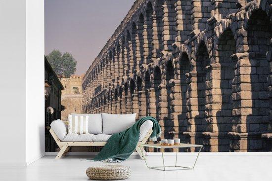 Fotobehang vinyl - Beeld langs het Romeinse aquaduct van Segovia breedte 360 cm x hoogte 240 cm - Foto print op behang (in 7 formaten beschikbaar)