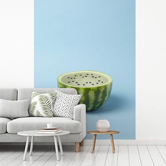 Fotobehang vinyl - Halve watermeloen met blauwe binnenkant op blauwe achtergrond breedte 165 cm x hoogte 220 cm - Foto print op behang (in 7 formaten beschikbaar)
