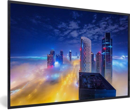 Foto in lijst - De hoogbouw Dubai steekt in de nacht boven de wolken uit fotolijst zwart 60x40 cm - Poster in lijst (Wanddecoratie woonkamer / slaapkamer)
