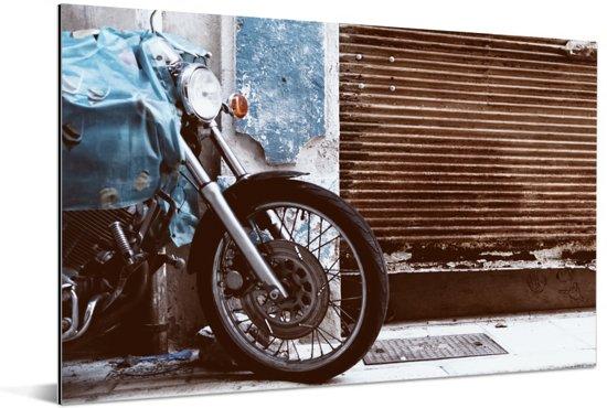 Een geparkeerde motorfiets met een roestige garagedeur Aluminium 60x40 cm - Foto print op Aluminium (metaal wanddecoratie)