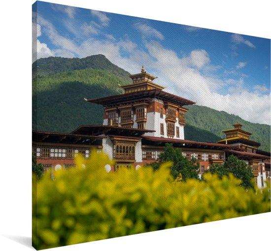 Foto van het Punakha Dzong klooster met gele bloemen op de voorgrond Canvas 30x20 cm - klein - Foto print op Canvas schilderij (Wanddecoratie woonkamer / slaapkamer)