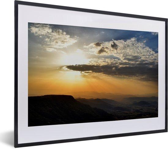 Foto in lijst - Zonsondergang over Lalibela in Ethiopië fotolijst zwart met witte passe-partout klein 40x30 cm - Poster in lijst (Wanddecoratie woonkamer / slaapkamer)