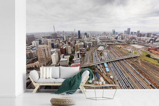 Fotobehang vinyl - Een bovenaanzicht van de stad Johannesburg in Zuid-Afrika breedte 390 cm x hoogte 260 cm - Foto print op behang (in 7 formaten beschikbaar)