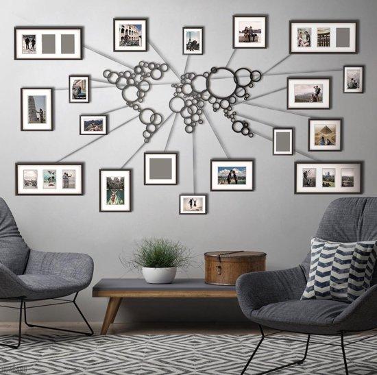 Metalen wereldkaart met foto's van reisavonturen aan de muur.