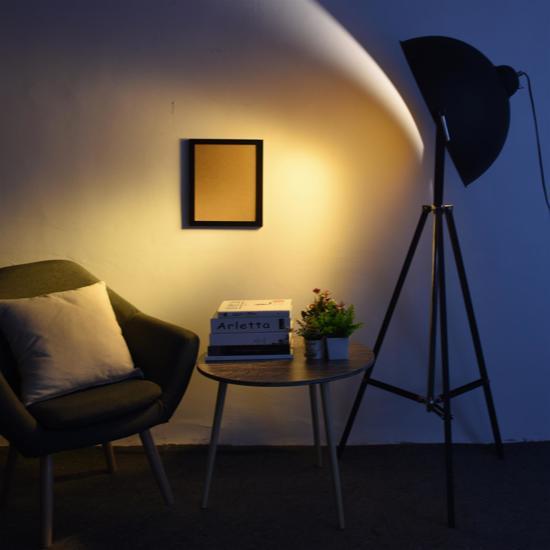Industriële driepoot vloerlamp in een duistere woonkamer die schijnt op een stoel met bijzettafeltje.