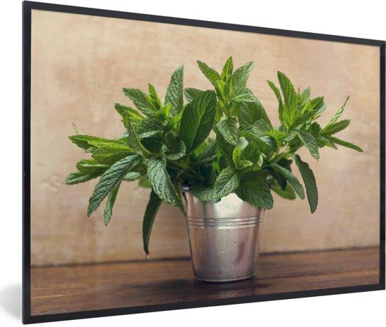 Foto in lijst - Een metalen vaas tot de nok toe gevuld met muntbladeren fotolijst zwart 60x40 cm - Poster in lijst (Wanddecoratie woonkamer / slaapkamer)