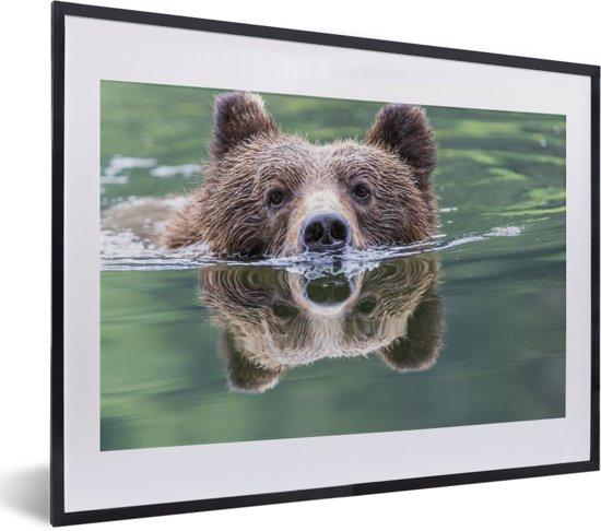 Foto in lijst - Een Grizzlybeer zwemt in het blauwe water fotolijst zwart met witte passe-partout klein 40x30 cm - Poster in lijst (Wanddecoratie woonkamer / slaapkamer)