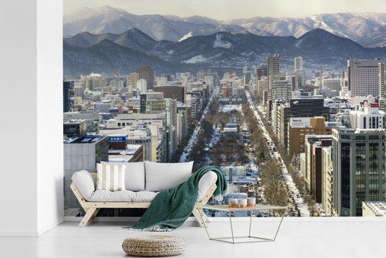 Fotobehang vinyl - Een prachtige foto van Sapporo-shi in de winter met op de achtergrond het hooggebergte breedte 330 cm x hoogte 220 cm - Foto print op behang (in 7 formaten beschikbaar)