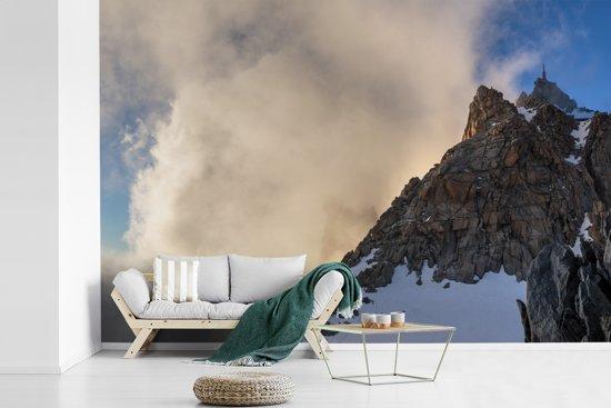 Fotobehang vinyl - Wolken boven de Aiguille du Midi berg in Frankrijk breedte 420 cm x hoogte 280 cm - Foto print op behang (in 7 formaten beschikbaar)