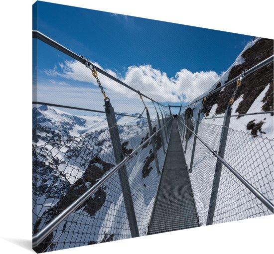 Een hangbrug met uitzicht op het besneeuwde landschap Canvas 180x120 cm - Foto print op Canvas schilderij (Wanddecoratie woonkamer / slaapkamer) XXL / Groot formaat!