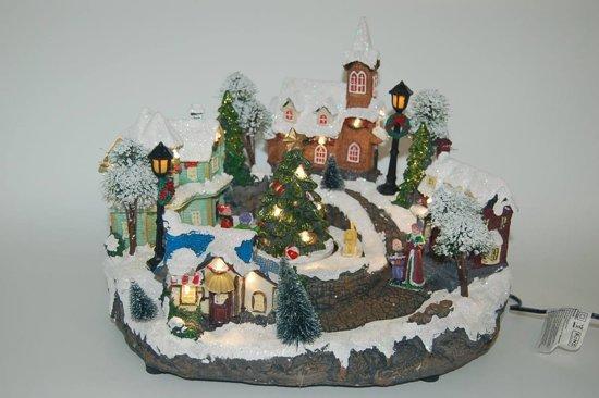 Kerstdorp met draaiende  kerstboom  en witte lichtjes