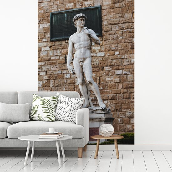 Fotobehang vinyl - Het standbeeld van David van Michelangelo voor een stenen muur breedte 270 cm x hoogte 400 cm - Foto print op behang (in 7 formaten beschikbaar)
