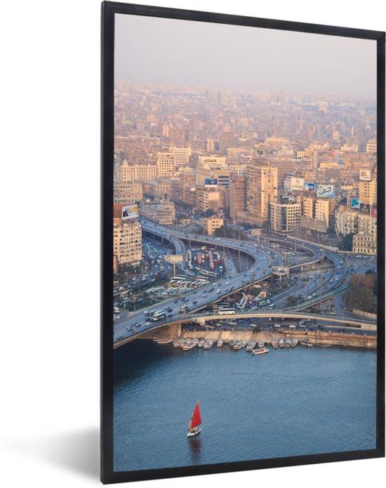 Foto in lijst - Rode zeilboot vaart over de Nijl in de Egyptische stad Caïro fotolijst zwart 40x60 cm - Poster in lijst (Wanddecoratie woonkamer / slaapkamer)