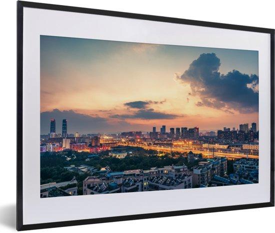 Foto in lijst - Zonsondergang achter de wolken in de Chinese stad Kunming fotolijst zwart met witte passe-partout 60x40 cm - Poster in lijst (Wanddecoratie woonkamer / slaapkamer)