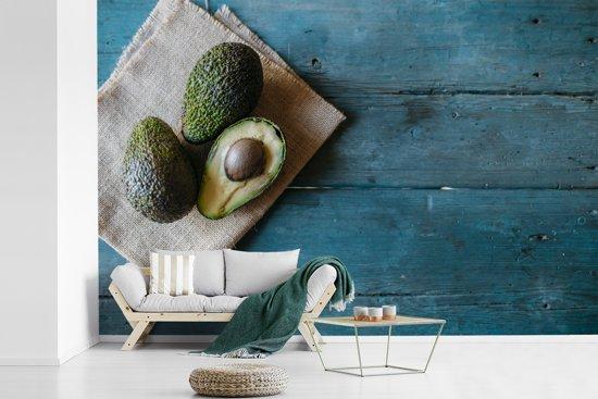Fotobehang vinyl - Avocado's op theekleed op een blauwe tafel breedte 540 cm x hoogte 360 cm - Foto print op behang (in 7 formaten beschikbaar)