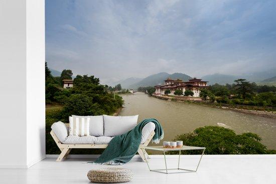Fotobehang vinyl - Grijze lucht boven het Punakha Dzong klooster en de Mo Chhu rivier breedte 390 cm x hoogte 260 cm - Foto print op behang (in 7 formaten beschikbaar)