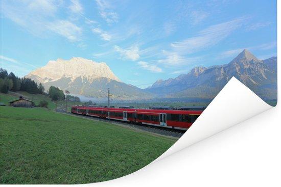 Een trein die rijdt door een  grasland Poster 180x120 cm - Foto print op Poster (wanddecoratie woonkamer / slaapkamer) XXL / Groot formaat!