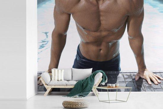 Fotobehang vinyl - Een gespierde man drukt zich op uit het zwembad breedte 305 cm x hoogte 220 cm - Foto print op behang (in 7 formaten beschikbaar)