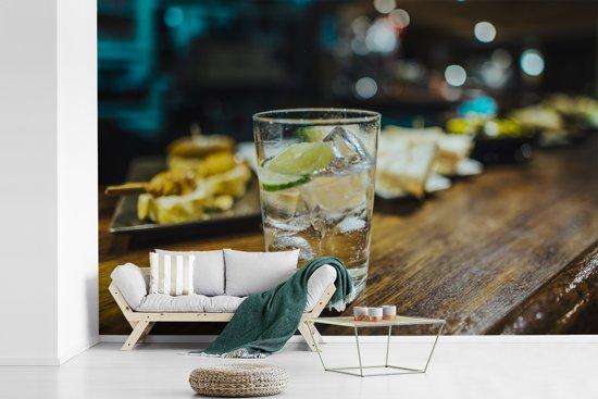 Fotobehang vinyl - Een gin tonic glas op een houten bar breedte 390 cm x hoogte 260 cm - Foto print op behang (in 7 formaten beschikbaar)