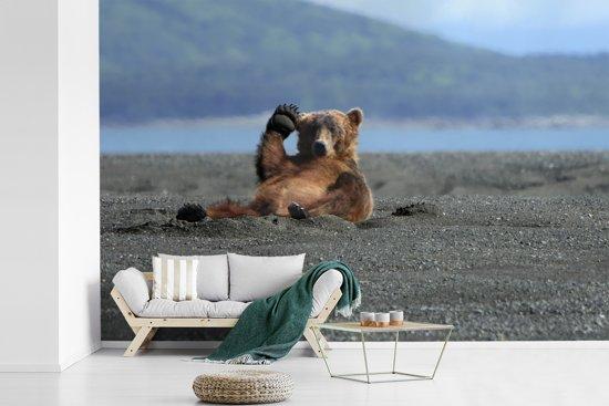 Fotobehang vinyl - Een Grizzlybeer zit te spelen in het zand bij het water breedte 390 cm x hoogte 260 cm - Foto print op behang (in 7 formaten beschikbaar)