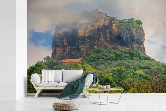 Fotobehang vinyl - Lion Rock tussen de wolken en mooie groene bomen er omheen breedte 330 cm x hoogte 220 cm - Foto print op behang (in 7 formaten beschikbaar)