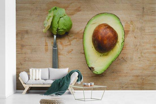 Fotobehang vinyl - Avocado op een snijplankje met een lepel breedte 390 cm x hoogte 250 cm - Foto print op behang (in 7 formaten beschikbaar)
