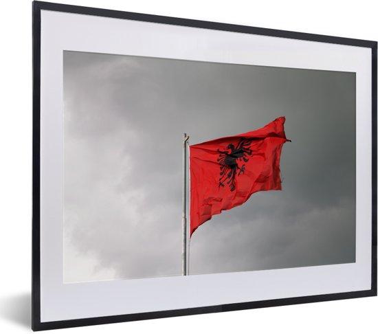 Foto in lijst - De vlag van Albanië wappert op een paal fotolijst zwart met witte passe-partout klein 40x30 cm - Poster in lijst (Wanddecoratie woonkamer / slaapkamer)