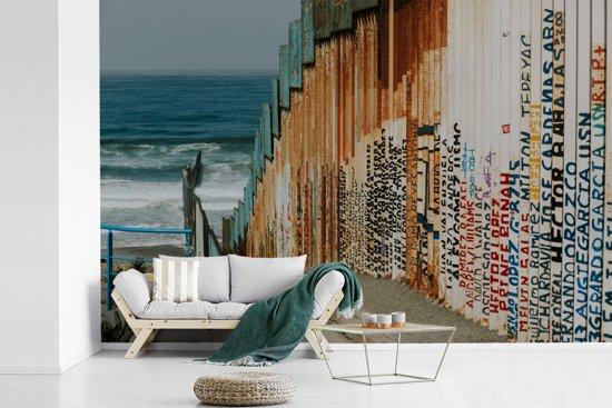 Fotobehang vinyl - Grens tussen Mexico en de VS bij Tijuana aan de Stille Oceaan breedte 390 cm x hoogte 260 cm - Foto print op behang (in 7 formaten beschikbaar)