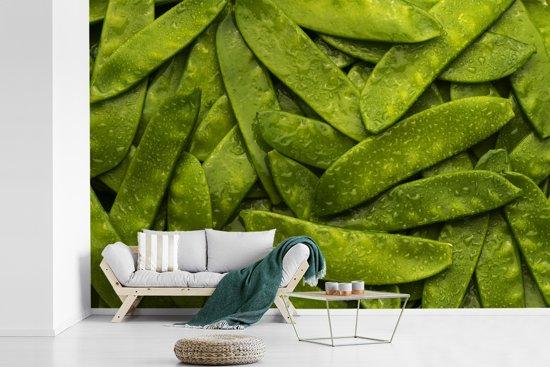 Fotobehang vinyl - Stapel van natte groene erwten in peulen breedte 600 cm x hoogte 400 cm - Foto print op behang (in 7 formaten beschikbaar)