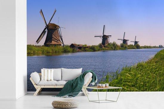 Fotobehang vinyl - Uitkijkend naar de Nederlande Molens van Kinderdijk in de middag breedte 390 cm x hoogte 260 cm - Foto print op behang (in 7 formaten beschikbaar)