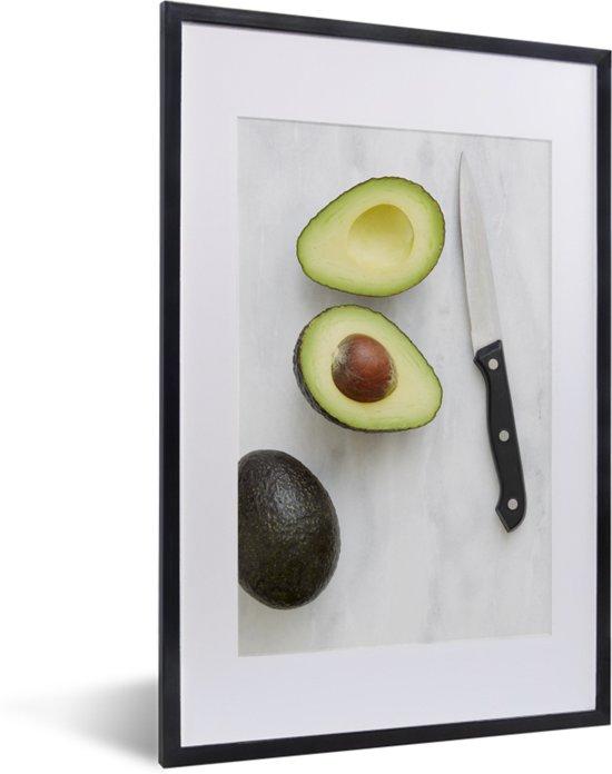Foto in lijst - Avocado gesneden met een mes fotolijst zwart met witte passe-partout 40x60 cm - Poster in lijst (Wanddecoratie woonkamer / slaapkamer)