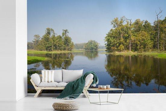 Fotobehang vinyl - Weerspiegeling in het water van een meer in het Nationaal park Chitwan in Nepal breedte 450 cm x hoogte 300 cm - Foto print op behang (in 7 formaten beschikbaar)