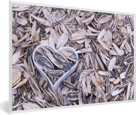 Foto in lijst - Zonnebloempitten met een hartvormige blik tussen de pitten fotolijst wit 60x40 cm - Poster in lijst (Wanddecoratie woonkamer / slaapkamer)