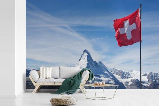 Fotobehang vinyl - De Zwitserse vlag in de bergen breedte 420 cm x hoogte 280 cm - Foto print op behang (in 7 formaten beschikbaar)