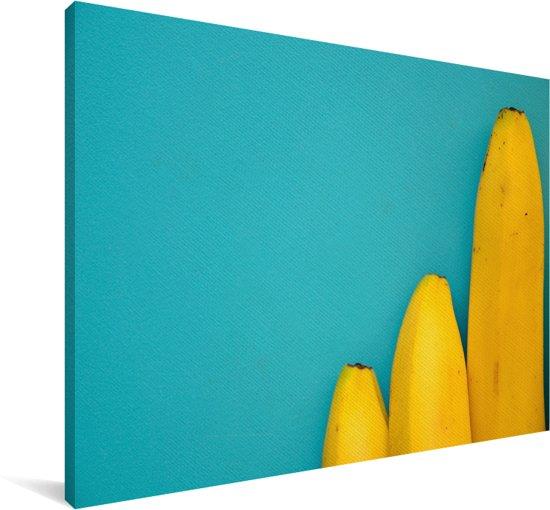 Bananen op lengte gelegd tegen een blauwe achtergrond Canvas 90x60 cm - Foto print op Canvas schilderij (Wanddecoratie woonkamer / slaapkamer)