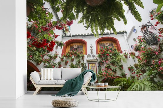 Fotobehang vinyl - Rode bloemen aan de muur in het Spaanse Córdoba breedte 360 cm x hoogte 240 cm - Foto print op behang (in 7 formaten beschikbaar)