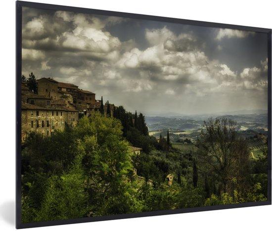 Foto in lijst - Wolken over de Toscaanse heuvels in de Italiaanse ommuurde stad San Gimignano fotolijst zwart 60x40 cm - Poster in lijst (Wanddecoratie woonkamer / slaapkamer)