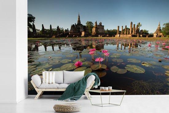 Fotobehang vinyl - Foto van mooie waterlelies in het water met op de achtergrond de tempels van Ayutthaya breedte 360 cm x hoogte 240 cm - Foto print op behang (in 7 formaten beschikbaar)
