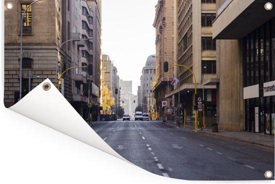 Een uitgestrekte weg tussen de hoogbouw in het centrum van Johannesburg in Zuid-Afrika Tuinposter 180x120 cm - Tuindoek / Buitencanvas / Schilderijen voor buiten (tuin decoratie) XXL / Groot formaat!