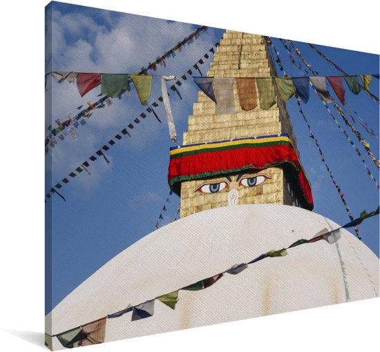 De ogen van Bouddhanath kijkend over de kleurrijke vlagjes die er hangen Canvas 180x120 cm - Foto print op Canvas schilderij (Wanddecoratie woonkamer / slaapkamer) XXL / Groot formaat!