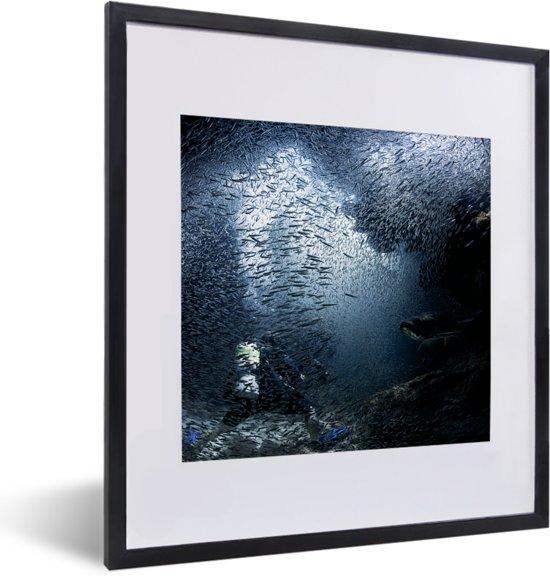 Foto in lijst - Duiker wordt in de grotten bij Grand Cayman ondergedompeld door vissen fotolijst zwart met witte passe-partout 40x50 cm - Poster in lijst (Wanddecoratie woonkamer / slaapkamer)