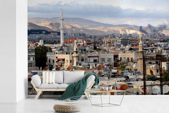 Fotobehang vinyl - Uitzicht op de daken van Damascus en de bergen in Syrië breedte 390 cm x hoogte 260 cm - Foto print op behang (in 7 formaten beschikbaar)