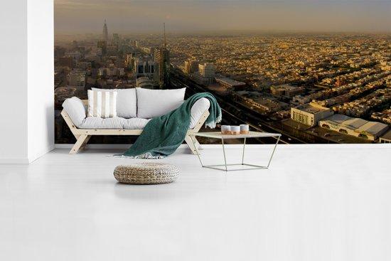 Fotobehang vinyl - Zonnestralen over de huizen in Riyad breedte 585 cm x hoogte 250 cm - Foto print op behang (in 7 formaten beschikbaar)