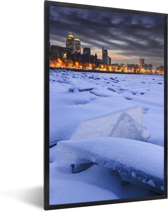 Foto in lijst - Een bevroren rivier voor de verlichte huizen van Dnipro in Oost-Europa fotolijst zwart 40x60 cm - Poster in lijst (Wanddecoratie woonkamer / slaapkamer)