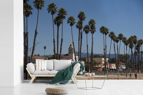 Fotobehang vinyl - Het stadslandschap van Santa Cruz Californië achter palmbomen breedte 360 cm x hoogte 240 cm - Foto print op behang (in 7 formaten beschikbaar)